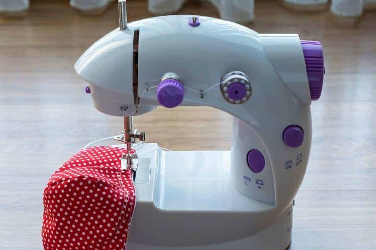 Mini Sewing Machine On a Wooden Floor