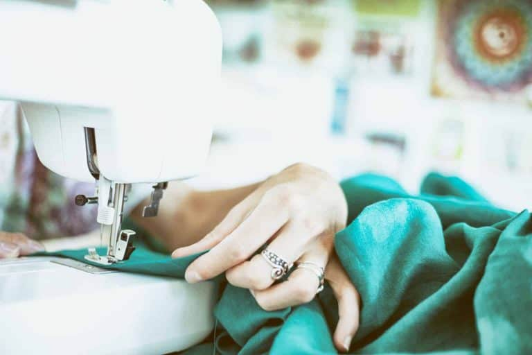 Person Sewing Green Fabric