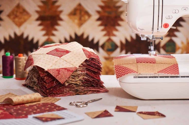 Quilting Machine Beside a Pile of Fabric