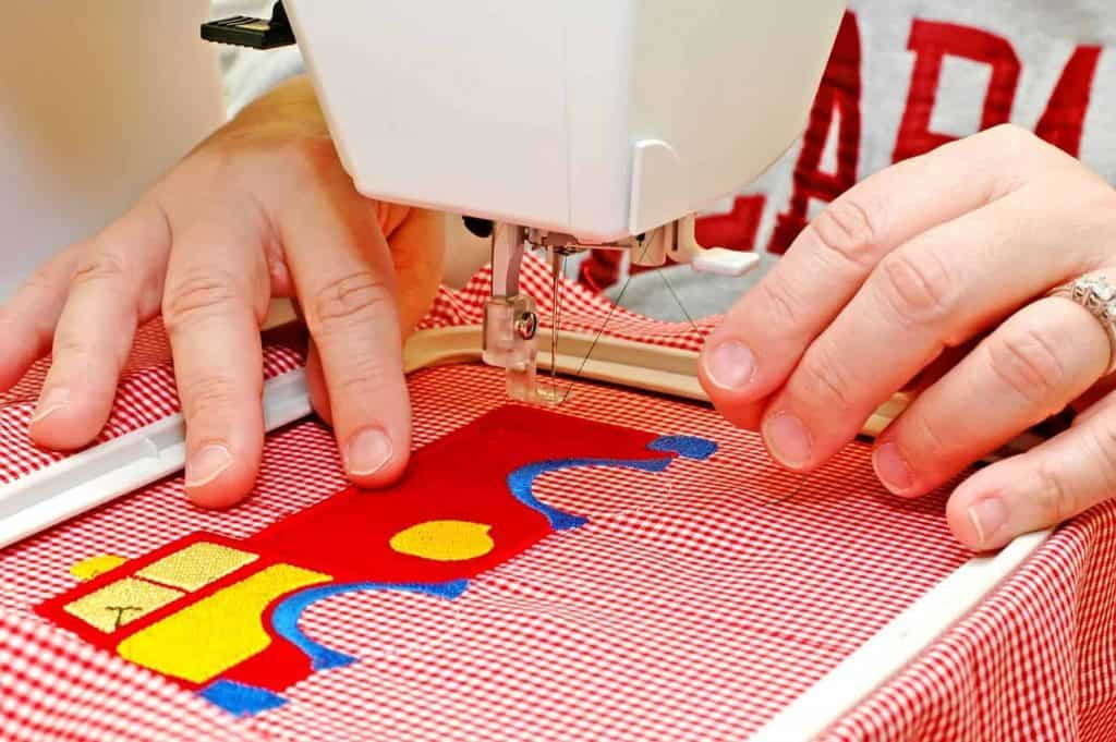 Sewing a Truck Pattern on Red Cloth