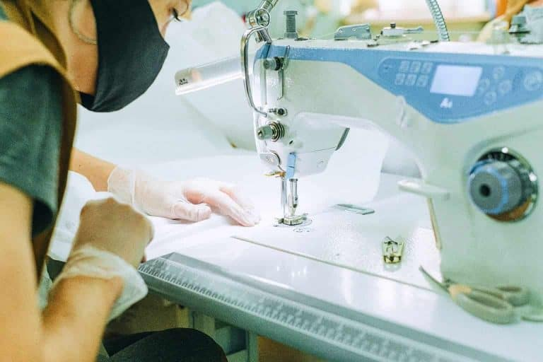 Woman Sewing White Fabric